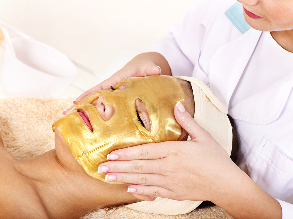 Facialist Applying Gold Sheet Mask on Client