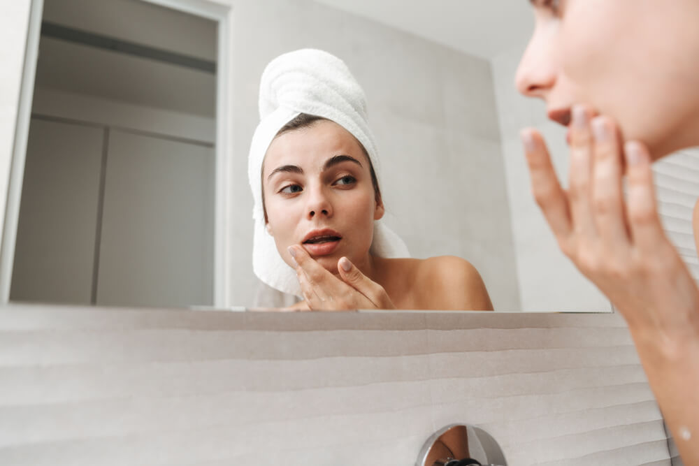 Woman checking her skin in the bathroom mirror