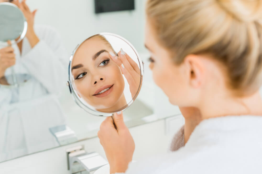 Beautiful woman looking at herself in handheld mirror