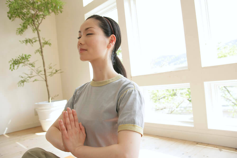 Calm and peaceful woman meditating at home