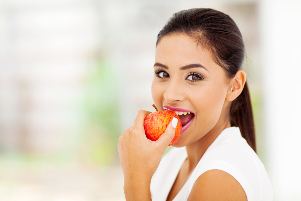 woman biting down on apple