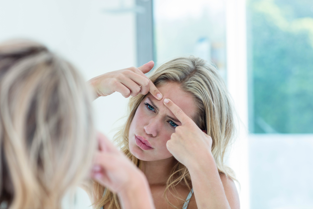 Blonde Woman Looking in Mirror Attempting to Squeeze Blemish