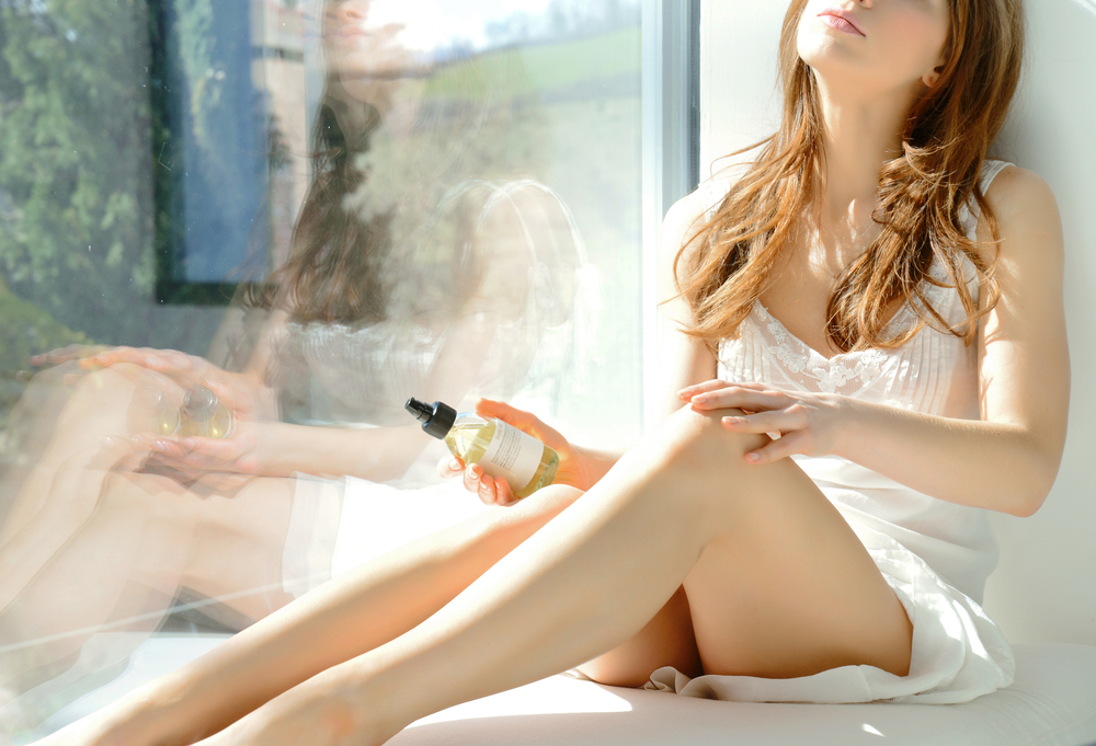 Woman Sitting by Window Holding Body Oil