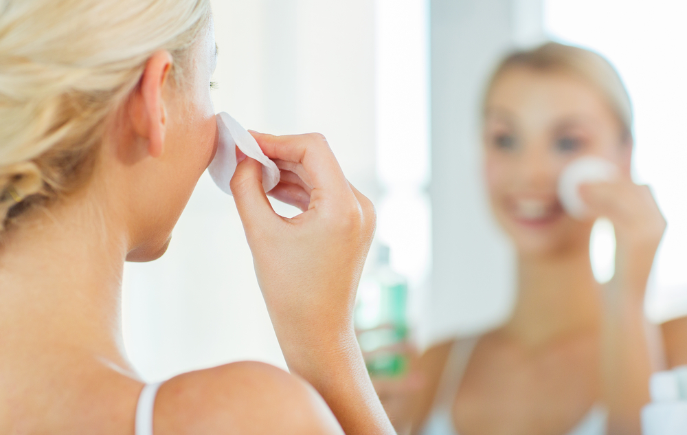 Woman Standing In Front of Mirror Wiping Face with Cotton Pad