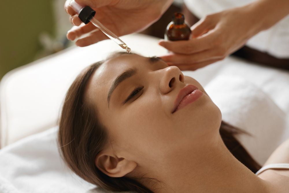 Facialist Applying Serum on Client's Forehead