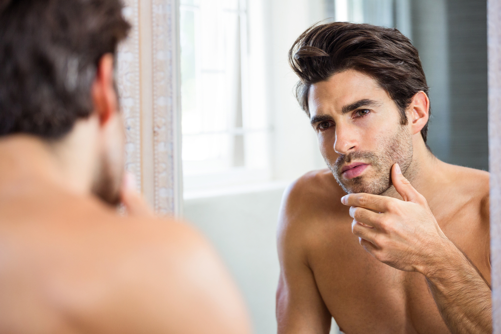 Man with Stubble Examining His Face in the Mirror