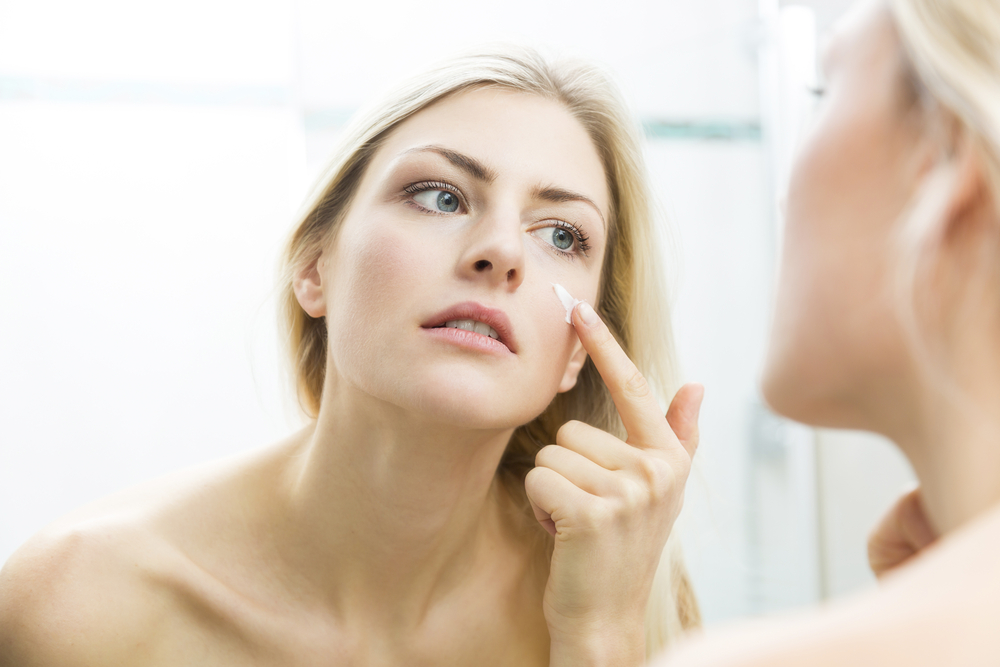 Blonde Woman Applying Skin Care Product