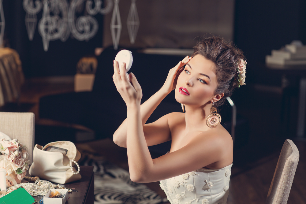 Beautiful Woman Holding Up Handheld Mirror Looking at her Skin