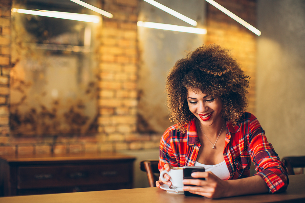 Woman Sitting with Coffee Cup and Cell Phone