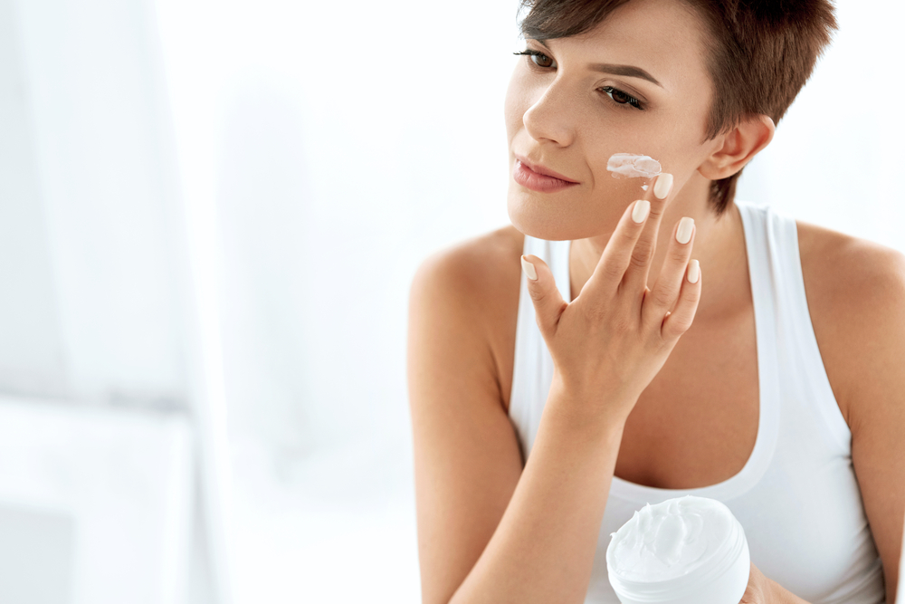 Woman applying skincare to face