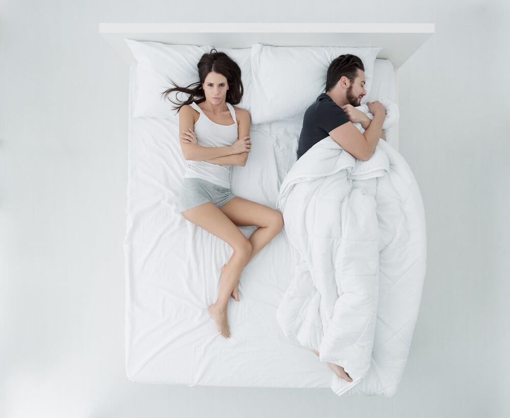 Couple in bed and woman has no blanket
