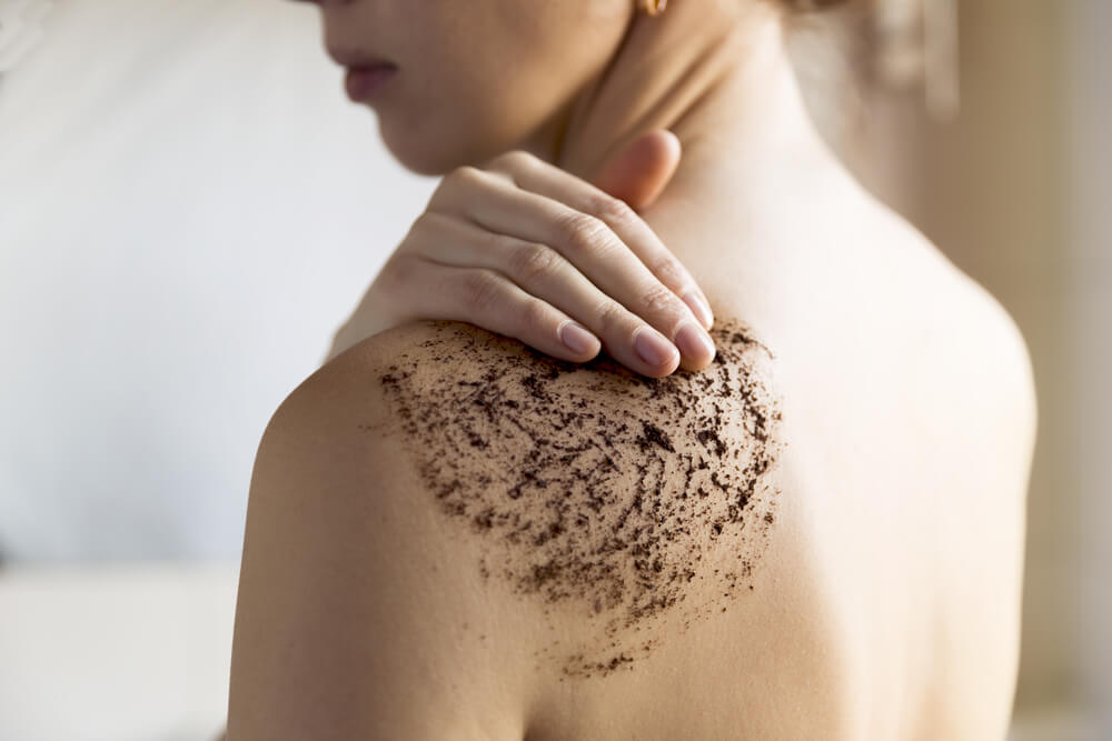 Woman using body scrub on back