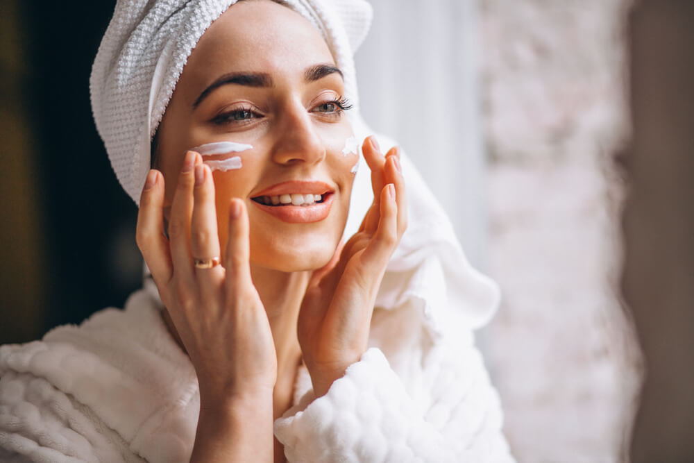 Woman applying OROGOLD 24K Deep Moisturizer to her face